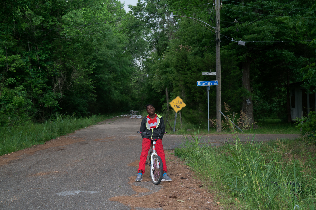 Jesse rides his bike along an abandoned street in St Irmal Lee. The tiny community has just 15 remaining homes and is surrounded by seven petro-chemical plants, three superfund sites and a massive landfill.